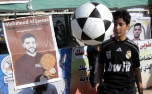 Palestinian boy plays with a football in front of banners in solidarity with Palestinian prisoner Mahmud Al-Sarsak in Rafah town. European athletes have joined in calls for the release of Palestinian footballer Mahmud Sarsak, who is on hunger strike in an Israeli prison. (AFP Photo/Said Khatib)