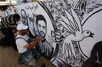 Palestinians paint a mural depicting Mahmoud al-Sarsak in southern Gaza on June 10, 2012 |Reuters/Ibraheem Abu Mustafa