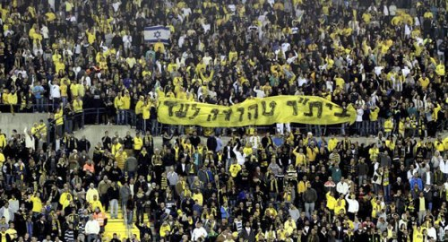"Supporters of Beitar Jerusalem hold a banner reading ""Beitar will always remain pure."" 