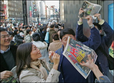 People gather to get extra newspapers reporting Japan's victory at the World Baseball Classic championship
