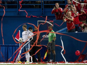 LA Galaxy David Beckham is covered in streamers handed out by management as he prepares to take a corner kick against Toronto FC during the first half of their quarter-final CONCACAF Champions League soccer match at the Rogers Centre in Toronto on March 7, 2012