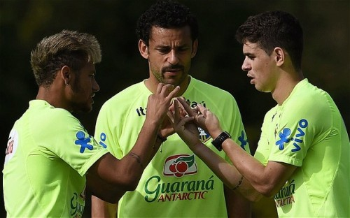 This is the plan: Oscar (right) talks tactics with Neymar (left) and Fred ahead of Brazil's last-16 game with Chile|GETTY
