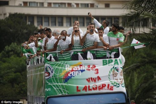 Algeria players take pictures on their phones as they are paraded through Algiers|Getty Images