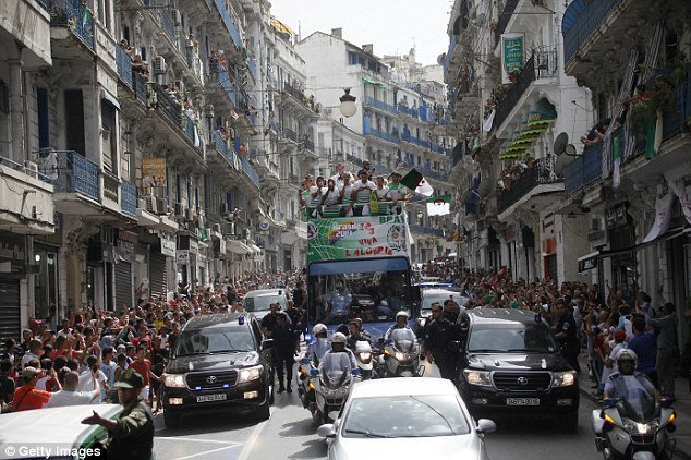 Homecoming: The Algerian squad are paraded through Algiers on an open-top bus on Wednesday