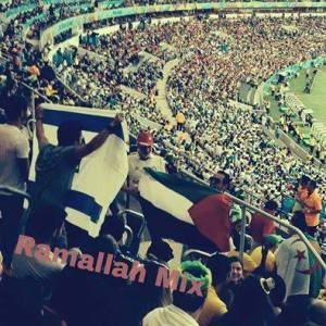 At a World Cup match in Brazil, an Algerian fan covers the flag of the Zionist usurping entity with the Palestinian flag