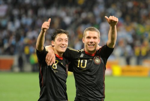 Germany's Mesut Oezil (L) and Lukas Podolski celebrate after the 2010 FIFA World Cup quarterfinal match between Argentina and Germany at the Green Point Stadium in Cape Town, South Africa 03 July 2010 |Marcus Brandt dpa