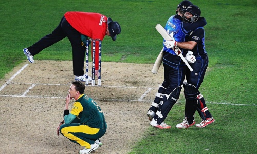 Daniel Vettori and Grant Elliott embrace as Dale Steyn thinks about what might have been. Elliott walked over to offer the bowler a hand up | Hannah Peters/Getty Images (Click to enlarge)