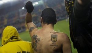 In this Tuesday, Jan. 29, 2013 photo, Beitar Jerusalem F.C. soccer supporters watch a State Cup soccer match against Maccabi Umm al-Fahm F.C. at the Teddy Stadium in Jerusalem | AP