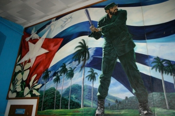 Photo shows a full-wall mural of Fidel Castro in the Cuban Baseball Hall of Fame showing his batting stance in front of a large Cuban flag, with palm trees and white doves. Photo by John Moist