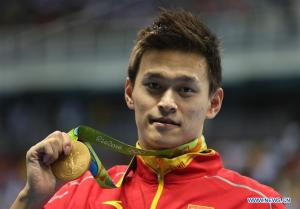 Sun Yang of China shows his medal during the awarding ceremony of men's 200m freestyle swimming final at the 2016 Rio Olympic Games in Rio de Janeiro, Brazil, on Aug. 8, 2016. Sun Yang won the gold medal with 1 minute 44.65 seconds | Xinhua/Fei Maohua