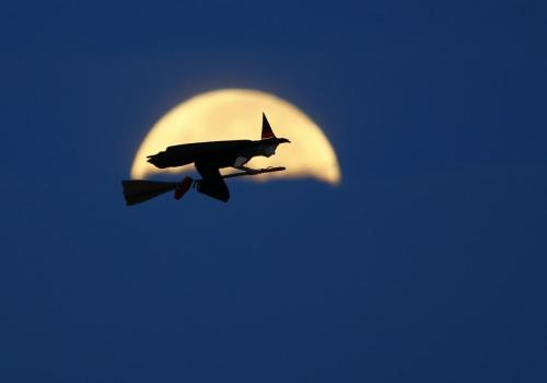 A radio-controlled flying witch flies past a moon setting into clouds along the pacific ocean in Carlsbad, California