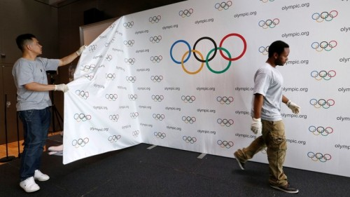 2016.06.21.ioc staff dismantle a backdrop after a news conference after the olympic summit on doping in lausanne, switzerland